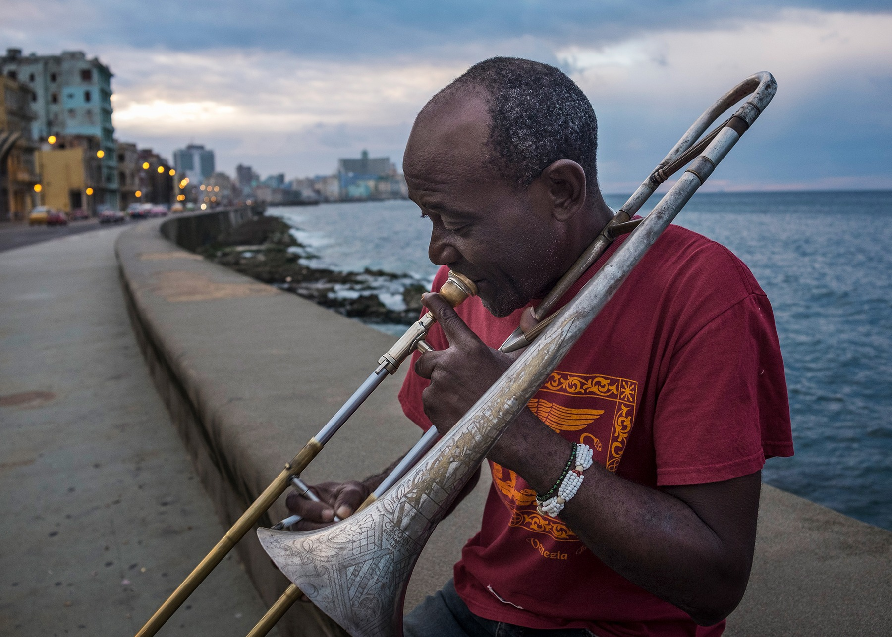 Man playing the trumpet on the malecon, cuba photo tours