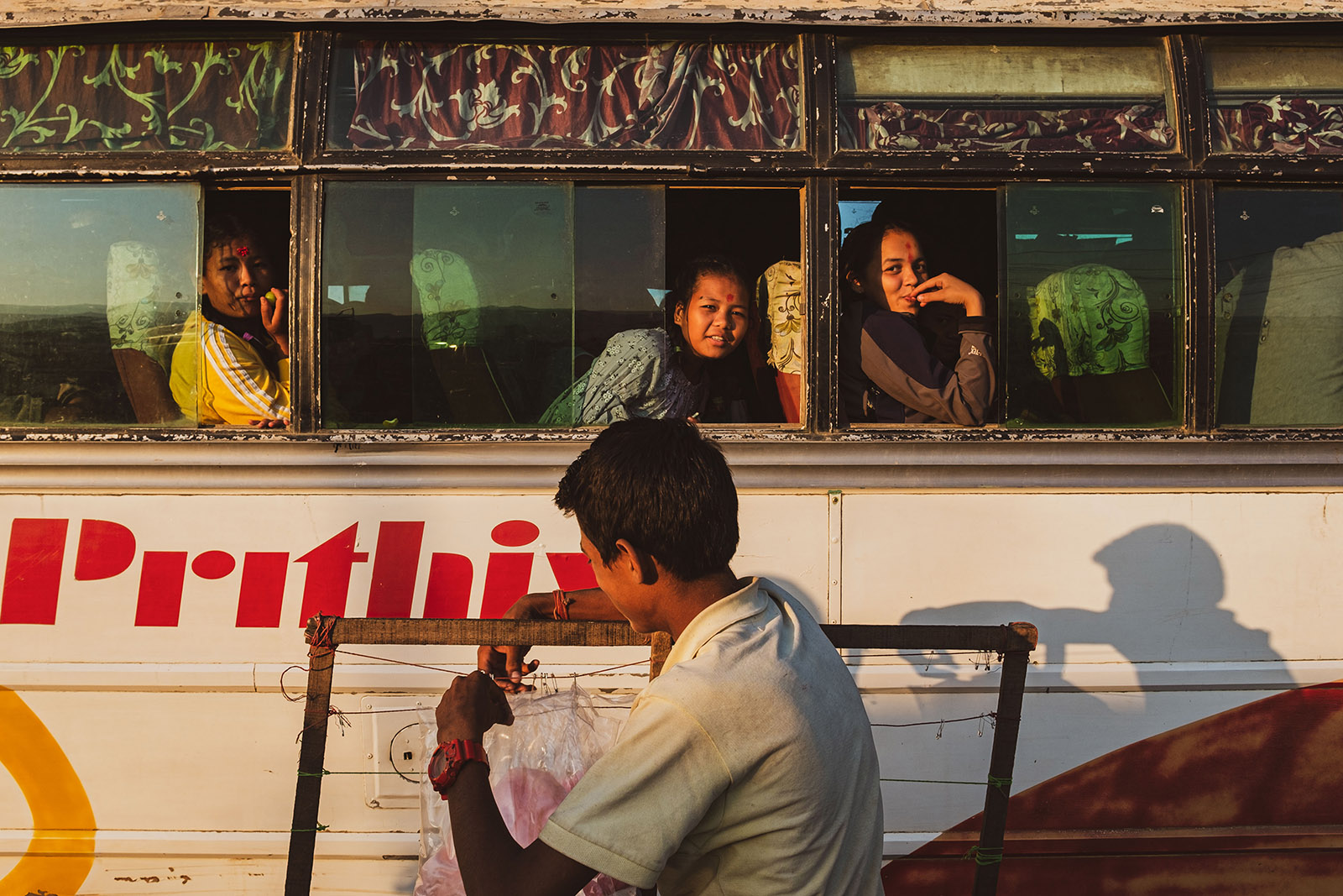 girls peer out of the bus window, Pokhara buspark