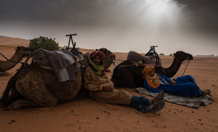 Camel guides rest on their camels, Merzouga, Morocco