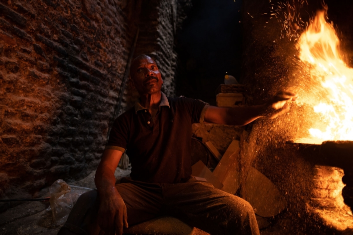 Man puts coal in the oven to heat the hammam, Marakech