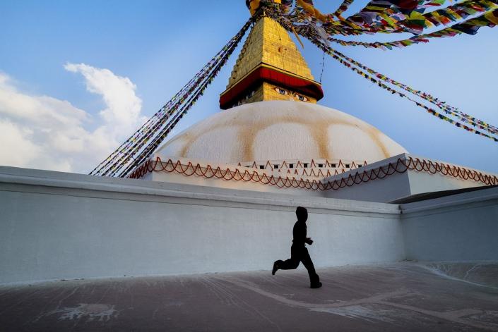 boy running at boudha temple in Kathmandu